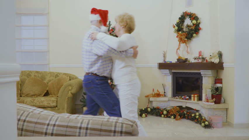 Happy mature woman dancing with husband near Christmas tree at home | Shutterstock HD Video #1011438761
