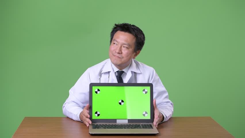 Mature Japanese man doctor against green background | Shutterstock HD Video #1011457121