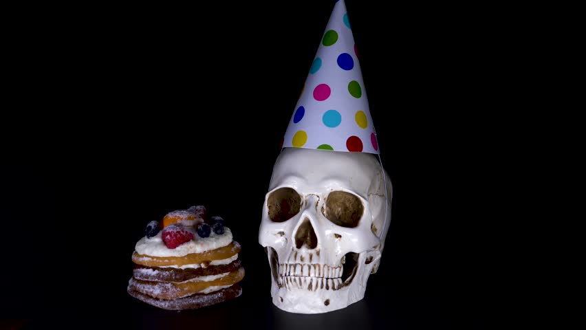 Cake and skull in a festive cap on a black background. candy, slow-motion shooting. 4k | Shutterstock HD Video #1011463241
