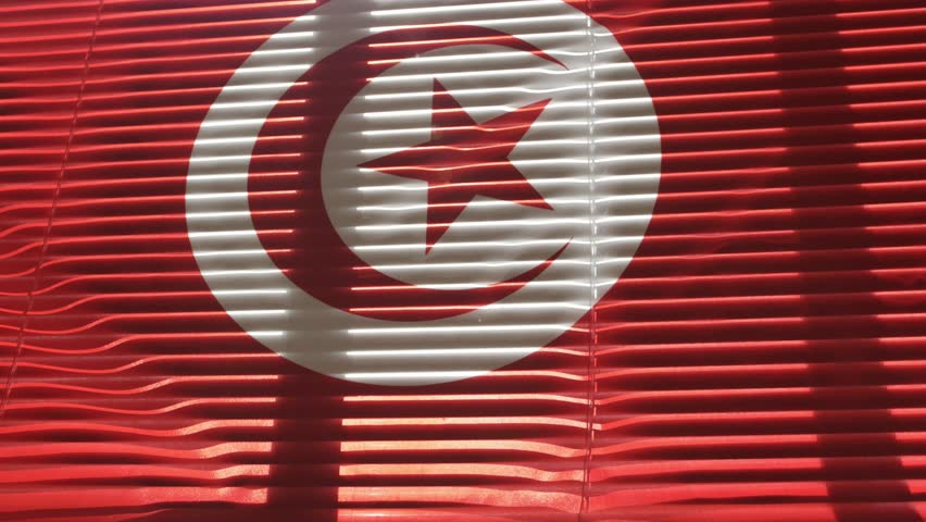 Tunisian flag hanging at wide jalousie window. Closeup  | Shutterstock HD Video #1011468851