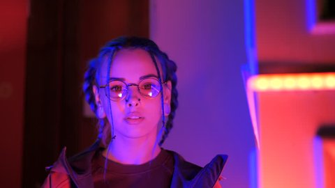 Young pretty girl with unusual hairstyle near glowing neon lights of the city at night. Dyed blue hair in braids. Serious hipster teenager in glasses and beautiful lenses.