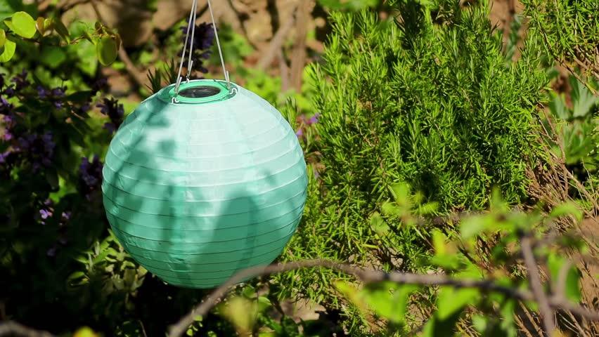 Tissue ball shaped lamp on solar batteries in garden. | Shutterstock HD Video #1011494201