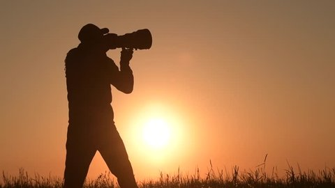 Men Taking Outdoor Pictures During Scenic Sunset. Photographer Silhouette. Telephoto Lens and the Modern Camera