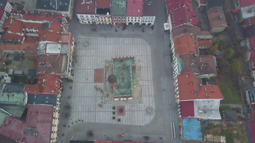 Foggy/Hazy Day in Tarnow Poland - 4k Tilt Up Drone Shot of Main Old Town Square, Colorful Red Roofed Buildings and Church During a Cold Morning | Shutterstock HD Video #1011505631