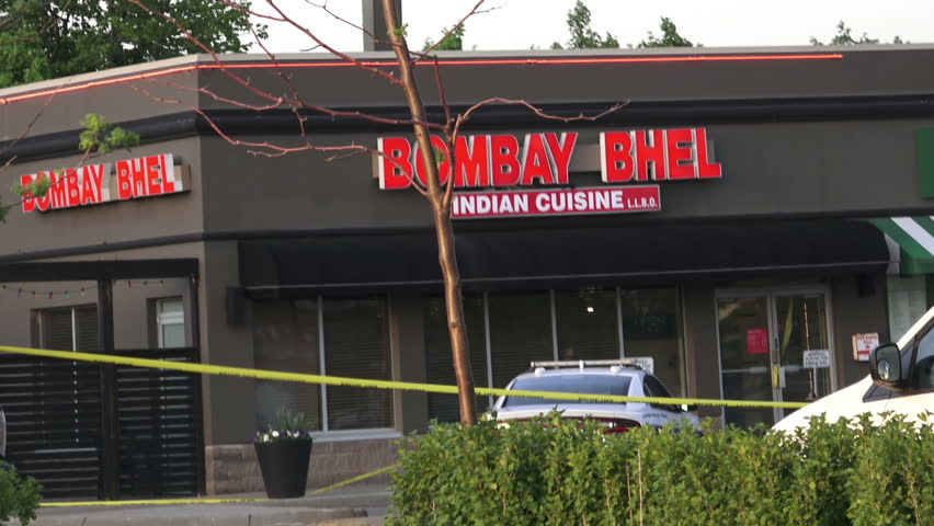 MISSISSAUGA CANADA - MAY 25, 2018: Yellow police tape corded part of a plaza in Mississauga where two masked men entered the Bombay Bhel restaurant and detonated an improvised explosive  device  | Shutterstock HD Video #1011509861