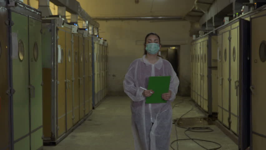Inspector in protective overalls write report after checking incubators   Shutterstock HD Video #1011522221