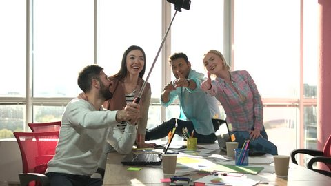 Co-workers taking photo usind selfie stick and playing the ape. Group of office workers taking picture of themselves with smartphone using selfie stick.