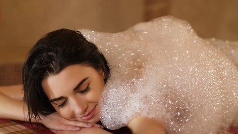 Woman covering by foam in hammam