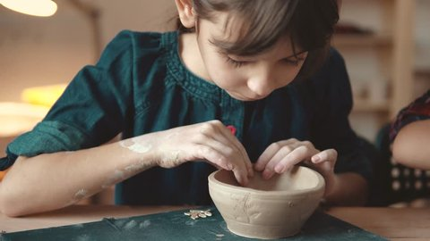 child is making a plate of clay. a lesson in pottery. little girl makes patterns on a clay stamp