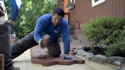 One man hands red bricks to another man who is putting the brick pavers into place in a herringbone pattern.