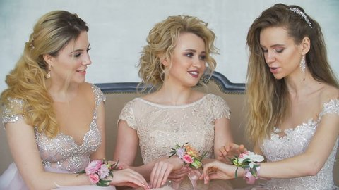 Three girls in dresses are sitting on the couch and are smiling closeup. On the hands of women are beautiful bracelets made of handmade flowers close up. 3 blondes laugh and tell stories in the day.