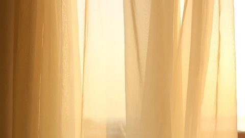 Curtains in the wind and summer sunlight