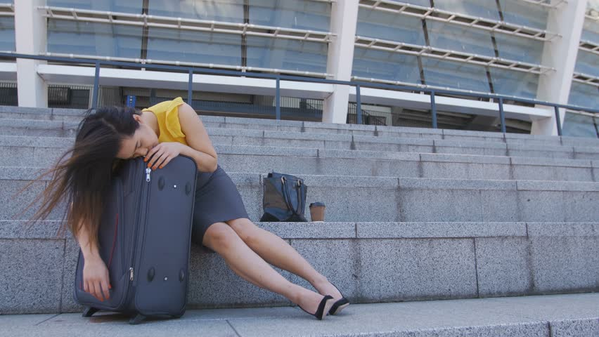 Full length of young asian business woman sleeping on suitcase outdoors near the airport during business trip. Tired exhausted corporate female taking nap after long working day during business travel | Shutterstock HD Video #1011620381