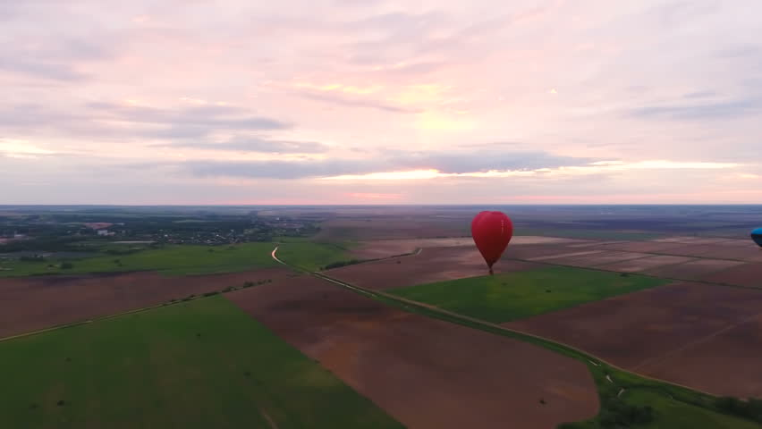 Red balloon in the shape of a heart.Aerial view:Hot air balloon in the sky over a field in the countryside.Aerostat fly in the countryside.