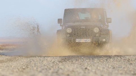 VIK, ICELAND - MAY 03, 2018. Jeep Wrangler Unlimited four wheel drive vehicledriving through puddle with big splash on gravel road