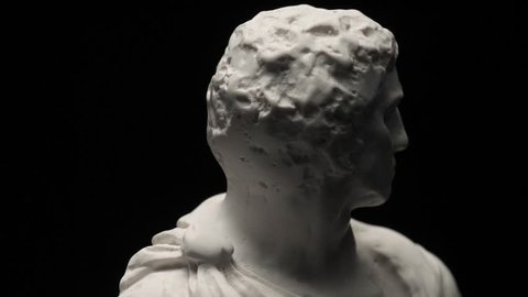 Ancient roman era white marble statue of Brutus rotating and showing every angles. Closeup shot with black background.