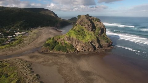 Aerial view of Lion Rock and large surf waves at Piha Beach, New Zealand