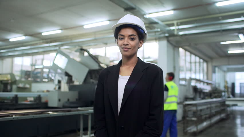 Portrait of african american boss woman in helmet and suit standing with arms crossed in big bright room in facility slow motion