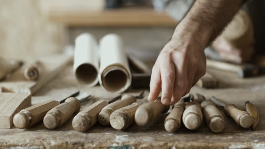 Professional skilled carpenter carving wood using mallet and chisel and set of woodworking tools in the foreground | Shutterstock HD Video #1011737561