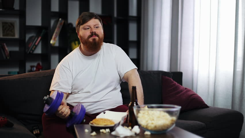 Funny fat guy eating fast food, drink beer and doing dumbbell training. He is sitting at home on the couch in front of the TV. Concept of malnutrition, sport, obesity