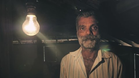 Light falls on a poor man's face after a tungsten light bulb slowly turns on or brighten up in old and traditional rural or village house. A farmer looking  when he first time receives electricity