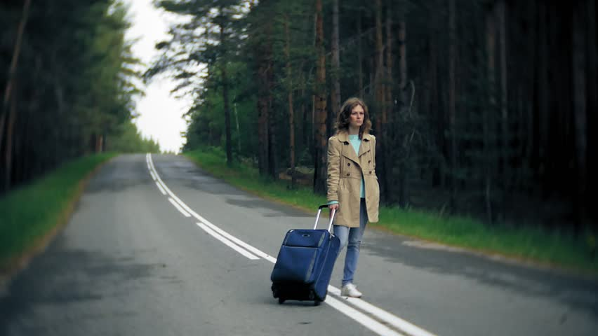 Young beautiful woman hitchhiking standing on the road with a suitcase on a table with an inscription SEA 4k