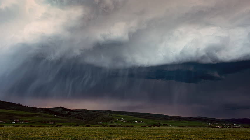Storm clouds rolling in the sky during rain storm in time lapse as it moves across the landscape and lightning strikes.