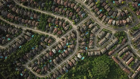 Aerial drone flight over a suburban community on a sunny summer day.  Roofs and backyard pools look bright and colorful. Trees and lawns are lush and green.