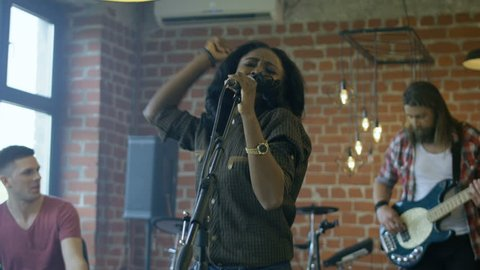 Stylish African-American woman singing into microphone having performance with rock band in studio