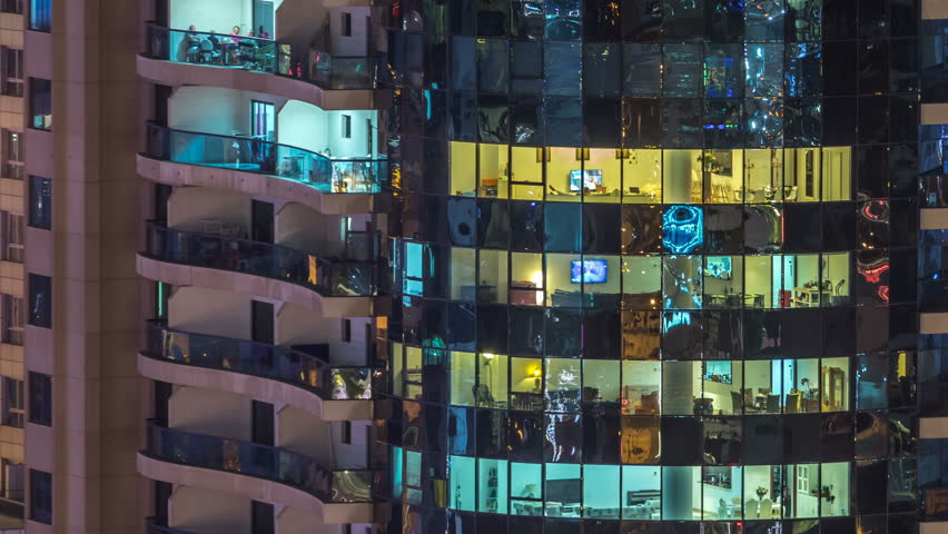 Windows of the multi-storey building of glass and steel lighting inside and moving people within timelapse. Aerial view of modern residential and office skyscrapers in Dubai marina. Pan right | Shutterstock HD Video #1011839951