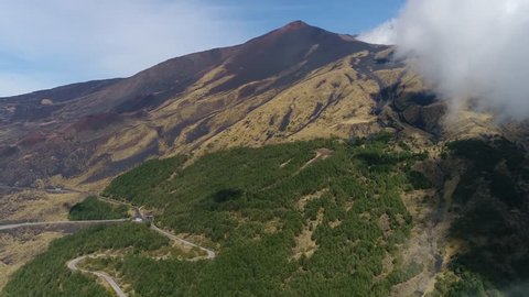 Aerial footage of Mount Etna emerging from clouds Etna an active stratovolcano on east coast of Sicily Italy in the Metropolitan City of Catania and is the highest active volcano in Europe 4k quality