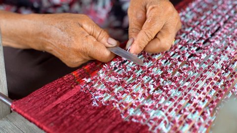 Thai Woman Take Off Ties from Mudmee Board Weaving or Ikat Thai Silk Pattern Weaving on Small Red Weaving Mill After Finish to Tie and Dyed in Thailand