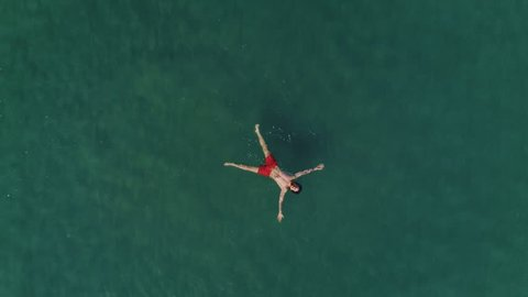 Aerial drone birdseye view shot of man in bright red swimming shorts lay flat on water surface of ocean sea, crystal clear see through turquoise waves, relaxed and chill vacation holiday deserved time
