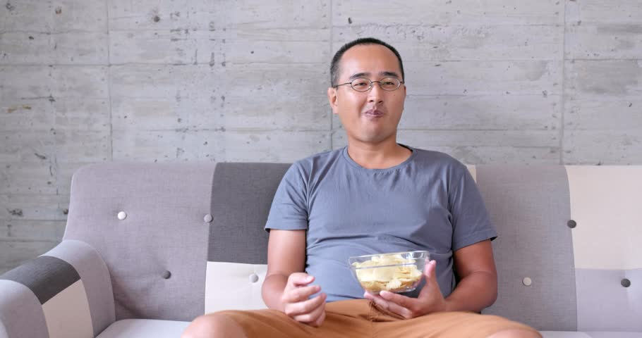 Man eating snack while watch movie at home