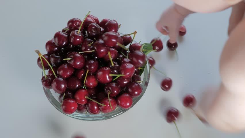Healthy food concept. Baby's hands awkwardly touch fresh juicy sweet cherries in glass deep plate on a white wooden table. Organic berries. Top view,  background, slow motion.