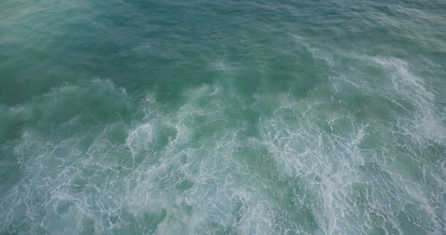 Drone flying backwards behind an ocean wave over amazing natural seafoam texture of blue and mint green rising up. | Shutterstock HD Video #1011914351