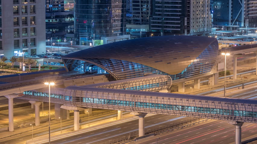 Aerial view of Metro station near Jumeirah lakes towers with illuminated skyscrapers night to day transition timelapse with traffic on sheikh zayed road and metro line. Rooftop view from Dubai marina