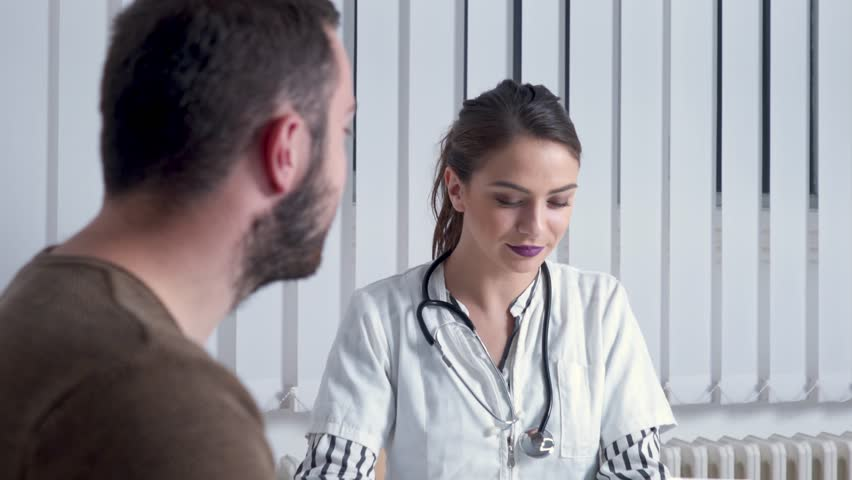 Female doctor using tablet for diagnostics. Young health professional uses tablet to explain health issues to a male patient, at her office.   Shutterstock HD Video #1011923711