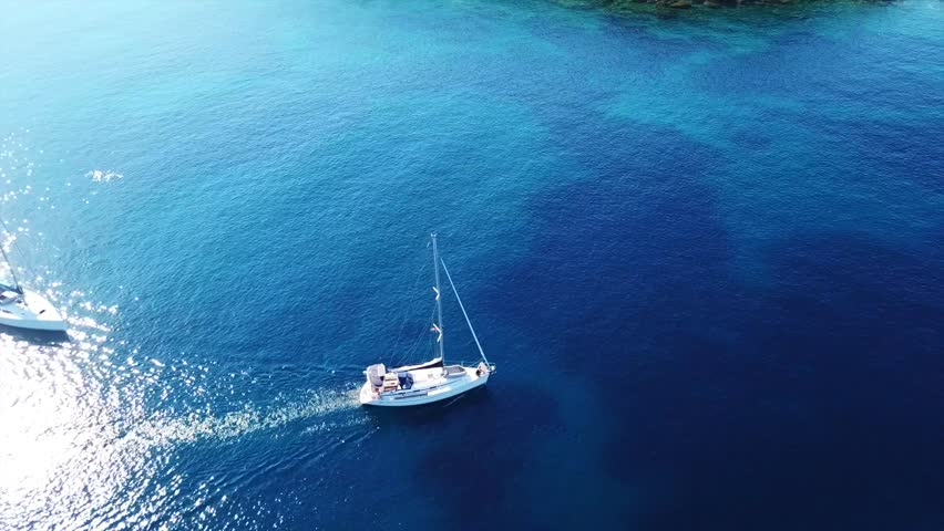 Aerial drone bird's eye view video of luxury yacht cruising in bay below archaeological site of Cape Sounio, Temple of Poseidon, Attica, Greece #1011926501