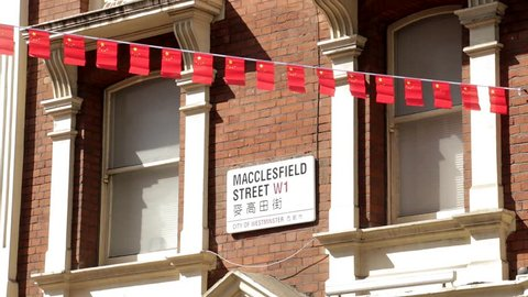 London, England - May 2018: Chinese flags sway gently in the breeze by the street sign in Macclesfield Street in London's Chinatown.