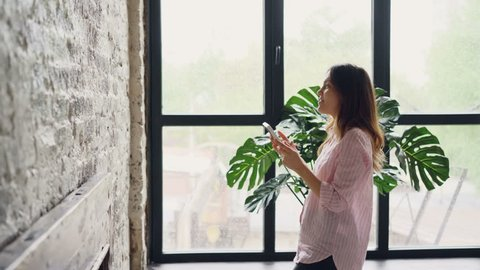 Pretty brunette house owner is decorating her loft style room hanging picture on brick wall choosing place. Interior design, housework, decorating apartment and people concept.