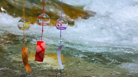 Japanese wind chimes with clean stream on the mountain river in the background.