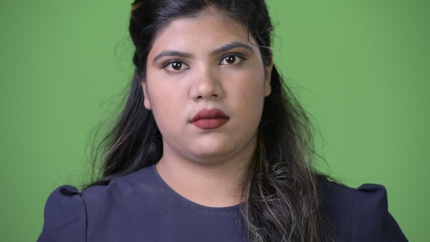 Young overweight beautiful Indian businesswoman against green background | Shutterstock HD Video #1011961901