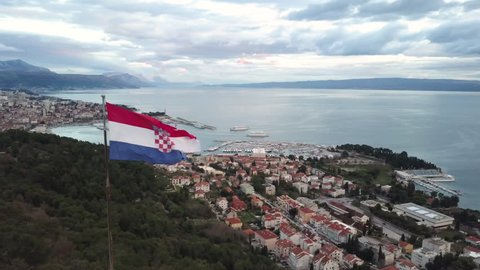 Croatia's Flag Filmed with Unique Drone Shot at Marjan Peak in the City of Split. Aerial Shot Arcing Around Flag Revealing Vast Cityscape and European Ocean