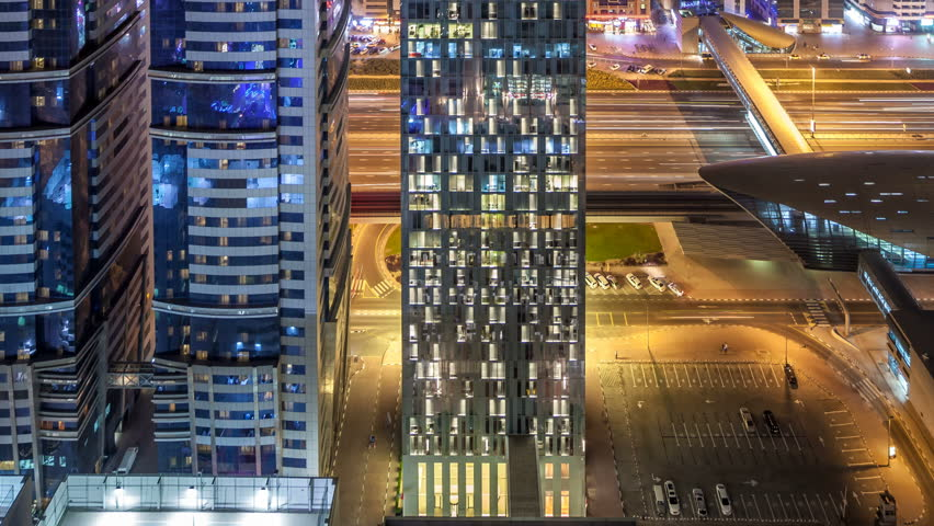 Skyline view of the buildings of Sheikh Zayed Road and DIFC night timelapse in Dubai, UAE. Illuminated skyscrapers in financial centre aerial view from above | Shutterstock HD Video #1011990311