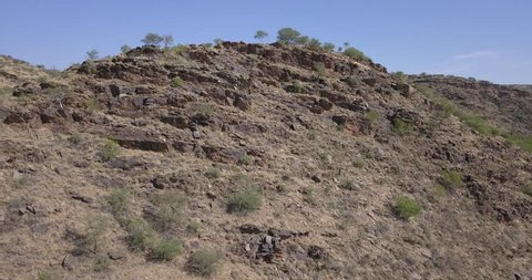 4K high quality aerial summer video of African savanna and riverbed surrounded by bush covered hills in Daan Viljoen National Reserve in Khomas Hochland area near Windhoek, Namibia's capital, Africa
