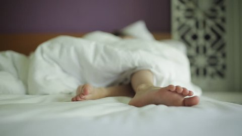 Close-up of the feet sleeping in the bed of a little girl