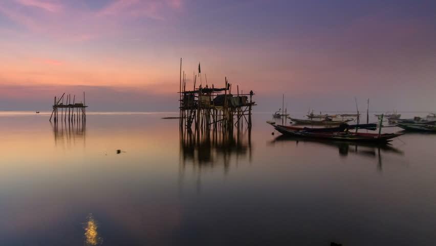 Timelapse of beautiful sunrise in Kenjeran beach. Kenjeran beach is located in Kenjeran district in the east Surabaya, Indonesia. Pan left camera motion.