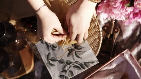 Close up of female hands open a small paper bag with cheese cut into cubes. Wine glasses. Picnic concept. Footage from the top