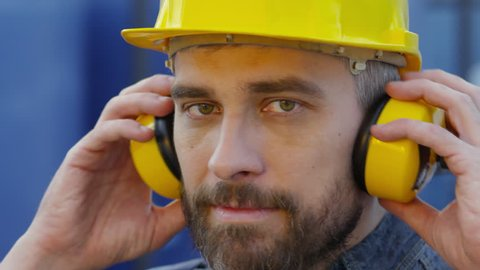 Close up face of bearded mature man in safety helmet taking off yellow earmuffs and looking at camera